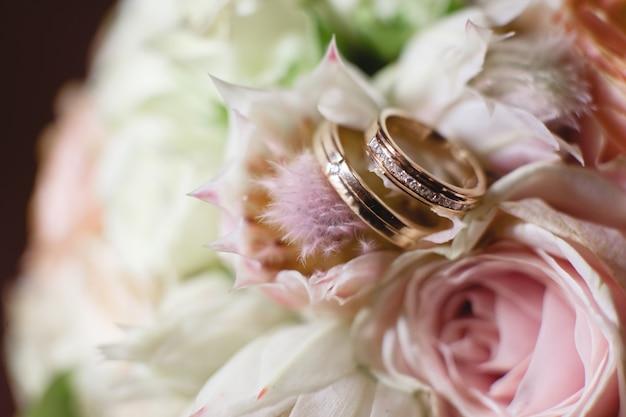 Złote obrączki ślubne na białej róży ze ślubu