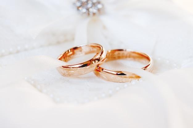 Złote obrączki ślubne na białym jedwabniczym tle. szczegóły ślubu. symbol miłości i małżeństwa.