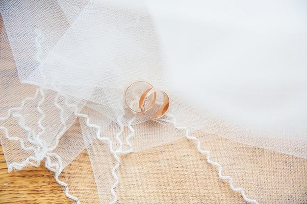 Złote obrączki ślubne na białym welonie