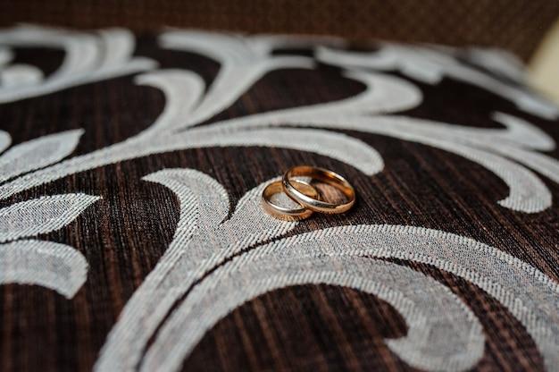 Złote obrączki ślubne na brązowej tkaninie