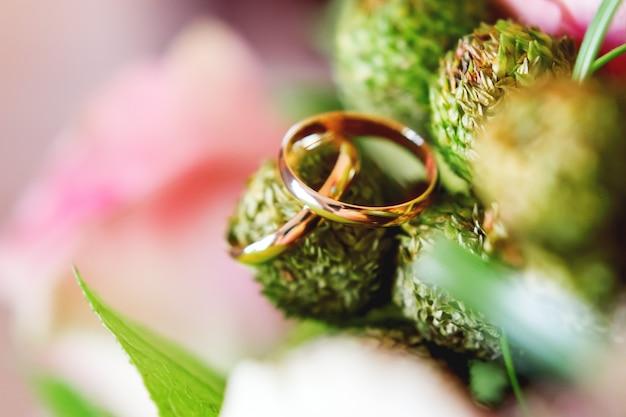 Złote obrączki ślubne na brunia kwiacie