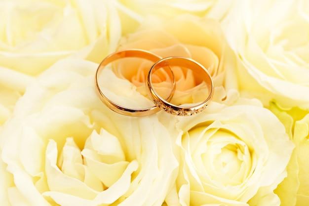 Złote obrączki ślubne na bukiecie kwiatów dla panny młodej