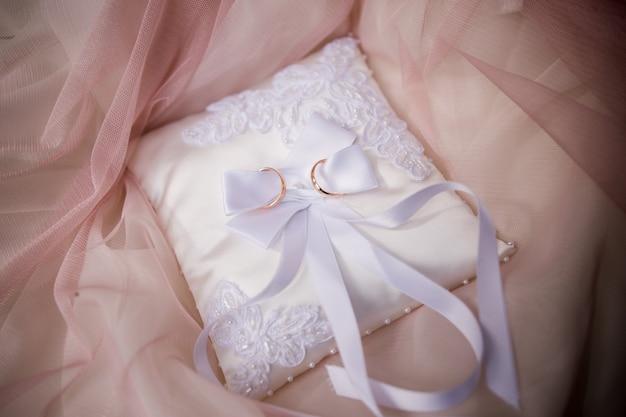 Złote obrączki ślubne na małej poduszce