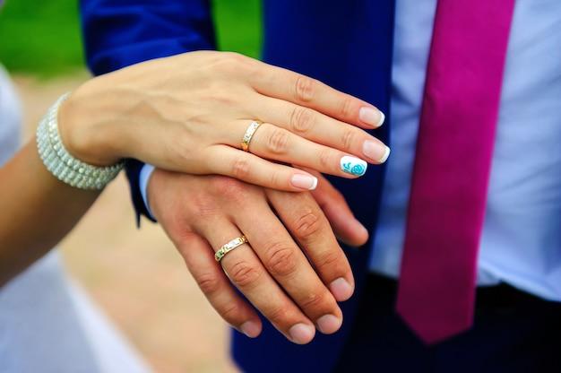 Złote obrączki ślubne na palcu pary młodej