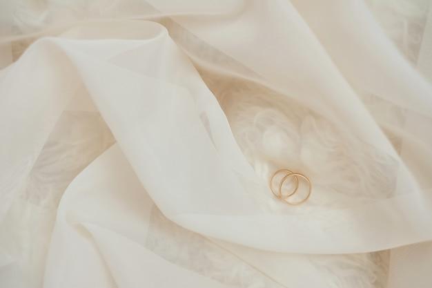 Złote obrączki ślubne na pastelowej koronki. płytka ostrość. jasne tło