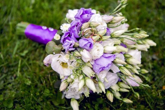 Złote obrączki ślubne na różach w bukiecie ślubnym