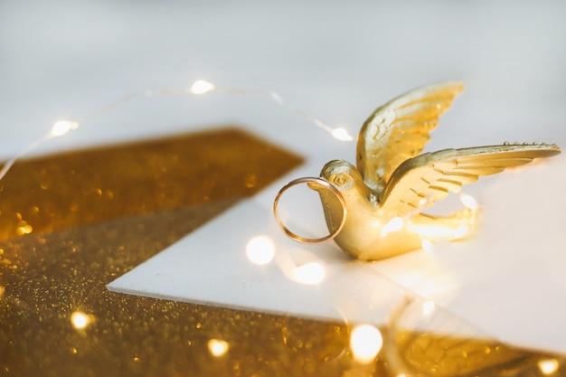Złote obrączki ślubne na złotym tle z zabawkowym ptakiem i dekoracjami.