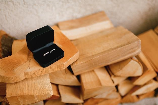 Złote obrączki ślubne w czarnym aksamitnym pudełku na posiekanym drewnie