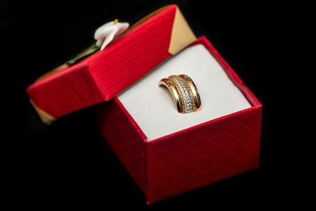 Złote obrączki ślubne w czerwonym pudełku na czarnym tle