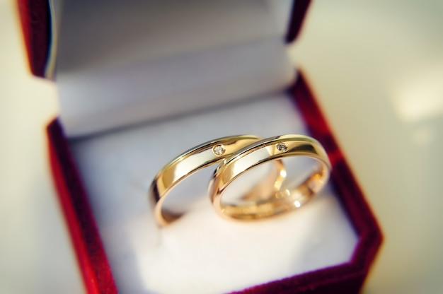 Złote obrączki ślubne w czerwonym pudełku