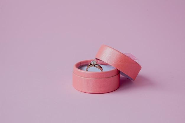 Złote obrączki ślubne w pudełku na różowym tle z miejsca na kopię.