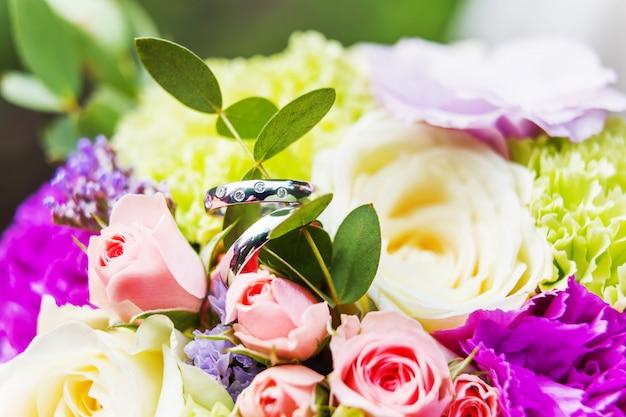 Złote obrączki ślubne z diamentami na bukiecie ślubnym