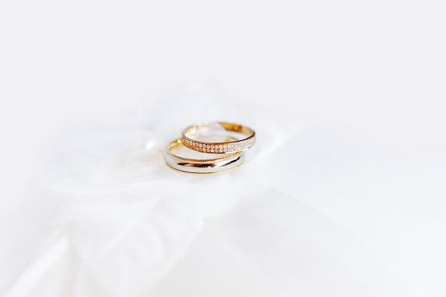 Złote obrączki ślubne z diamentami na tkaninie jedwabnej