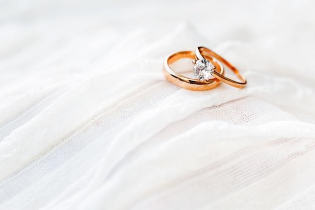 Złote obrączki ślubne z diamentem leżą na tkaninie onwhite. symbol miłości i małżeństwa.