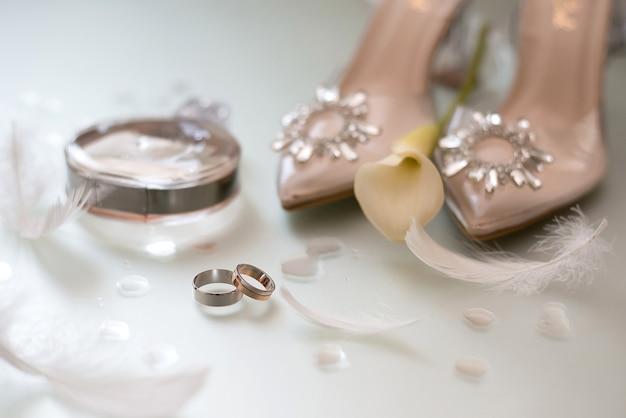 Złote obrączki ślubne z piórami obok beżowych butów panny młodej ozdobionych kamieniami na których leży żółty kwiat i obok flakonu perfum chanel