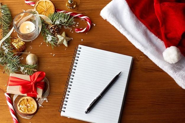 Złote ozdoby świąteczne, czapka mikołaja i otwarty pusty notatnik