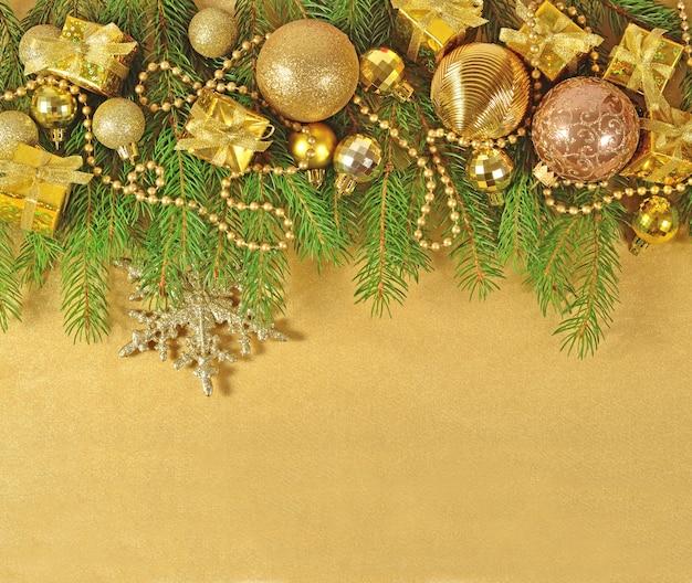 Złote ozdoby świąteczne na świerkowej gałęzi na złotym tle