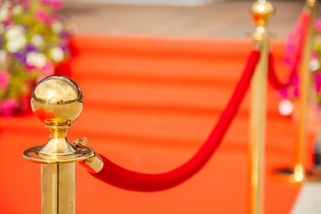 Złote paski strzegące czerwonego dywanu na imprezie