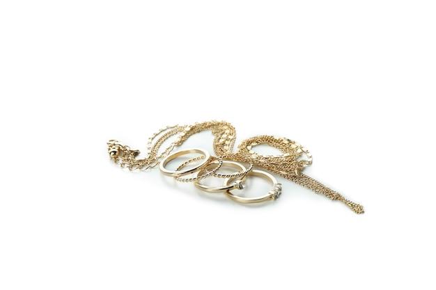 Złote pierścienie i łańcuch na białym tle