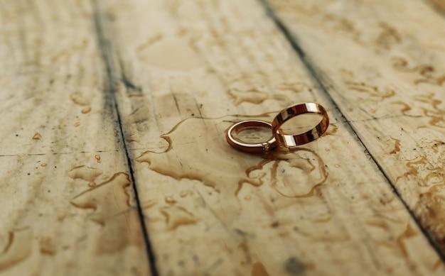Złote pierścienie na drewnianej ścianie koncepcja ślubu.