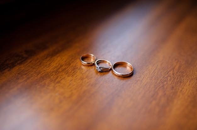 Złote pierścienie na drewnianym stole