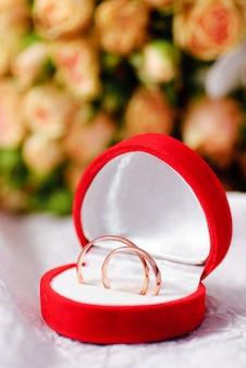 Złote pierścienie na tle bukiet róż. shallow dof, selektywna ostrość