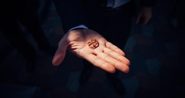 Złote pierścienie w dłoni mężczyzny w słońcu. dzień ślubu, uroczystość.