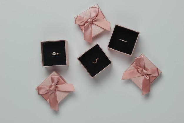 Złote pierścienie w pudełkach na prezent na białym tle. sklep jubilerski. widok z góry