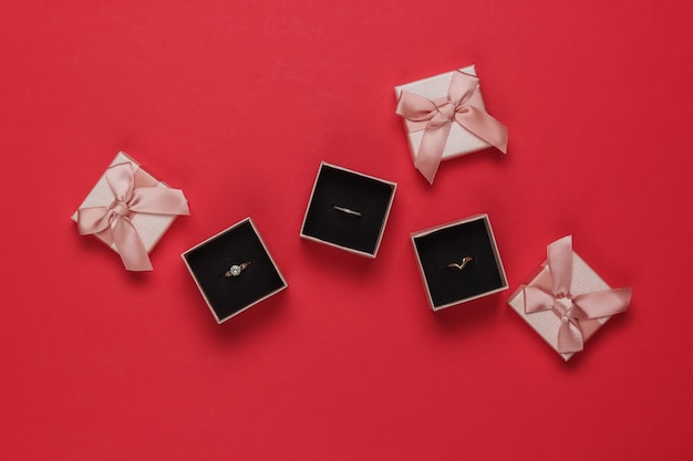 Złote pierścienie w pudełkach na prezent na czerwonym tle. sklep jubilerski. widok z góry