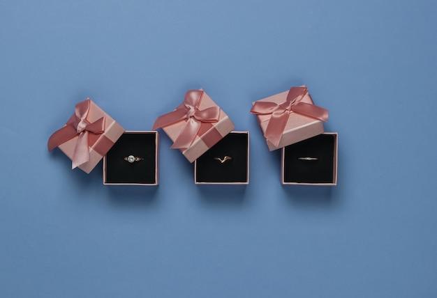 Złote pierścienie w pudełkach na prezent na niebieskim tle. sklep jubilerski. widok z góry