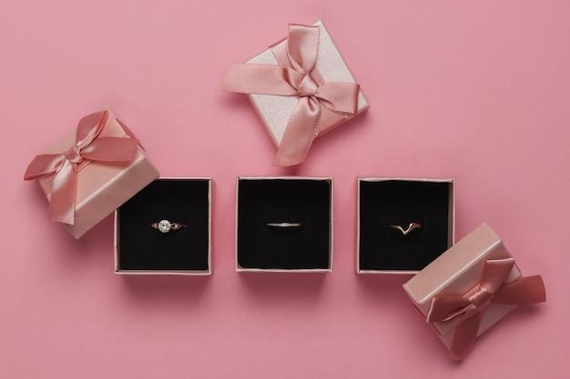 Złote pierścienie w pudełkach na różowym pastelowym tle. sklep jubilerski. widok z góry