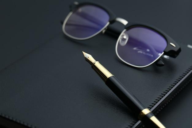 Złote pióro, notebook, kalkulator i okulary na czarnym biurku