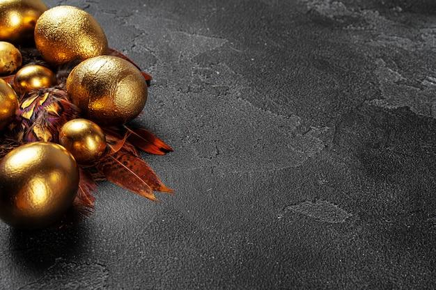 Złote pisanki na czarnej powierzchni betonu
