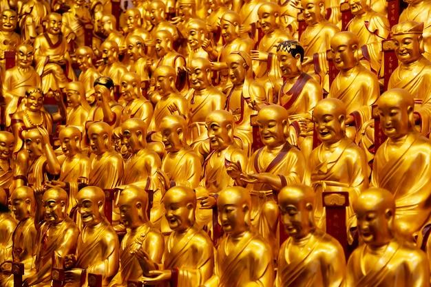 Złote posągi lohanów w świątyni longhua w szanghaju w chinach.