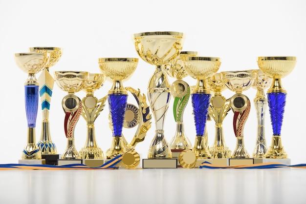 Złote puchary i medale dla zwycięzcy zawodów sportowych na białym stole.