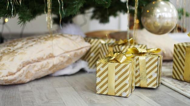 Złote pudełka z prezentami pod choinką