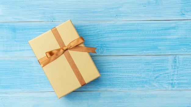 Złote pudełko na niebieskim drewnianym stole.