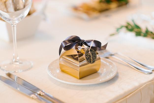Złote pudełko z bonbonniere z brązową satynową kokardką na talerzu do serwowania na stole bankietowym. dekoracje ślubne