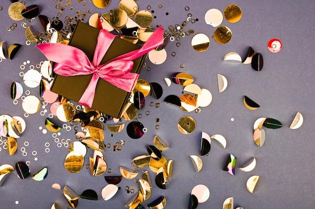 Złote pudełko z kokardą i konfetti