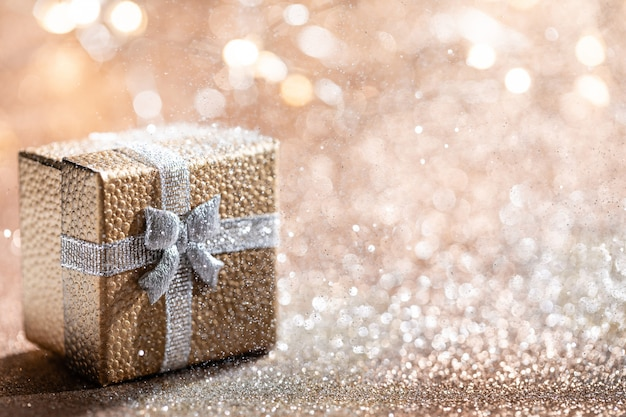 Złote pudełko z magicznym światłem na bokeh brokatowym na święta bożego narodzenia.