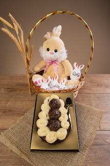 Złote pudełko z pół jajkiem wielkanocnym i pluszowym króliczkiem w tle.