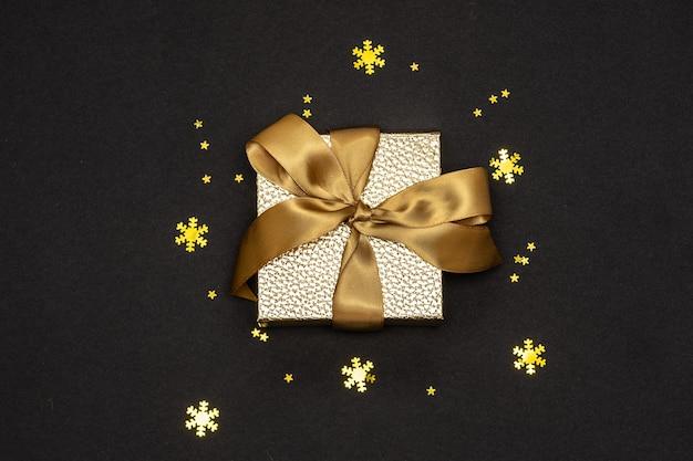 Złote pudełko ze wstążką i błyszczącymi dekoracjami na czarnym tle