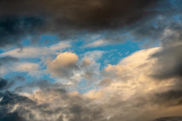 Złote, puszyste chmury oświetlone znikającymi promieniami o zachodzie słońca i dramatyczne ciemne chmury burzowe unoszące się po słonecznym błękitnym niebie, aby zmienić letnią pogodę. wspaniały widok naturalnego tła meteorologii.