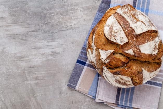 Złote rustykalne chrupiące bochenki chleba i bułeczki na drewnianym stole. martwa natura uchwycona z góry, widok z góry, płaski układ.