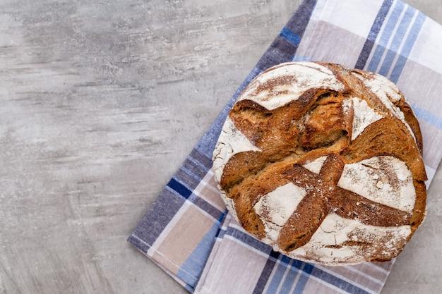 Złote rustykalne chrupiące bochenki chleba i bułeczki na podłoże drewniane. martwa natura uchwycona z góry, widok z góry, płaski układ.