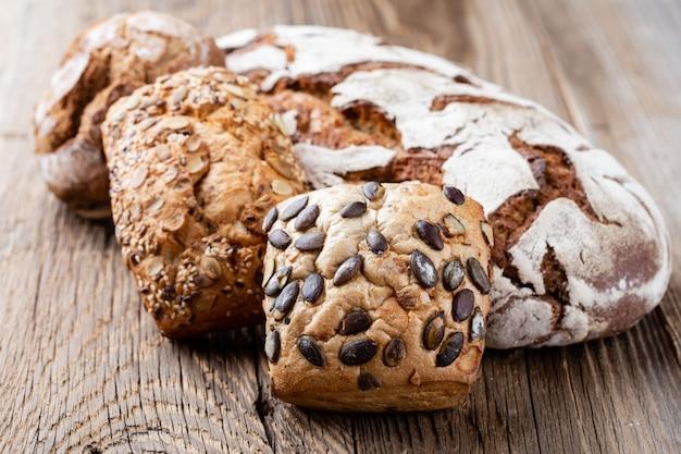 Złote rustykalne chrupiące bochenki chleba i bułeczki na podłoże drewniane