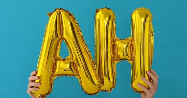 Złote słowo ah wykonane z nadmuchiwanych balonów