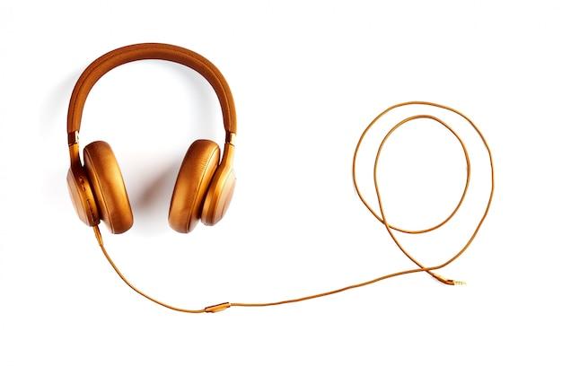 Złote słuchawki z drutem skręcone w spiralę na białym tle
