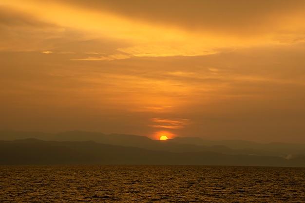 Złote światło wschodu słońca za górami i morzem.