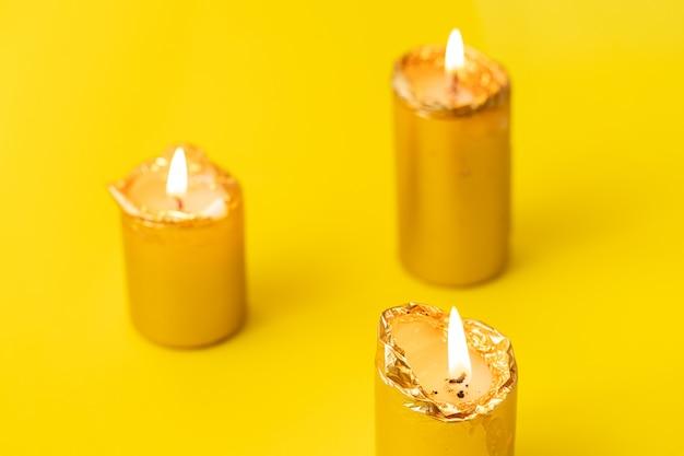 Złote świeczki na kolor żółty powierzchni. wellnes, magia, relaks koncepcja. przytulny dom